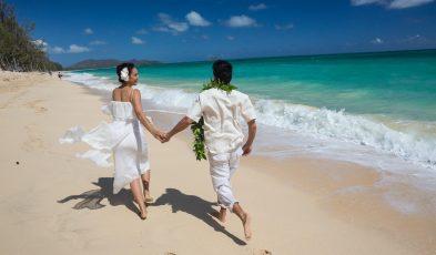Newlyweds run along Waimanalo Beach, Waimanalo, Oahu, Hawaii